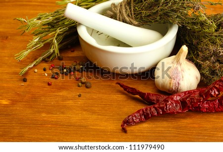 dried herbs in mortar and  vegetables, on wooden background