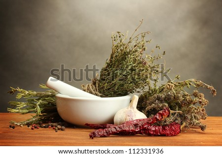 dried herbs in mortar and vegetables, on wooden table on grey background