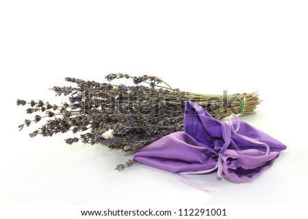 dried lavender flowers and lavender bags against white background