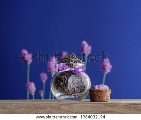 Dried lavender heap in a small glass jar on wood table at blur background with fresh flowers of lavanda in soft focus. Aromatic herb of Provence with a  decoration of cicada from France trip, closeup. Foto stock ©