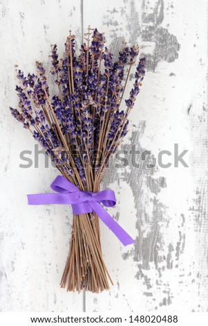 Dried lavender herb flowers tied in a bunch over distressed white wooden background.