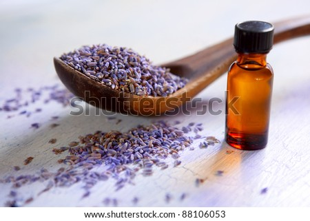Dried lavender with a bottle of essential oil on a rustic table