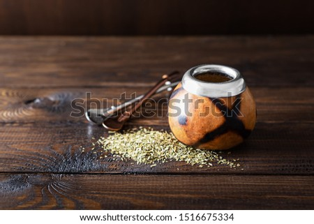 Dried mate tea leaves, high in caffeine, Calabasas and bombilla on a dark wooden background Foto stock ©