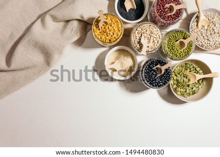 Dried mixed beans, Kidney Beans, red beans, mung beans, chickpeas, millet, minimal style photography with wooden spoon and wooden bowl, pan on white background
