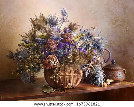 Dried multicolored flowers in a vase on the table.Pastel brown background.