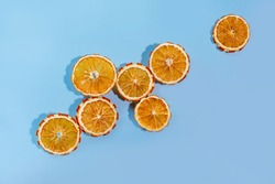 Dried orange slices in the sunlight with dark shadows on a blue background. Dry mechanism concept under the scorching sun, dehydration.