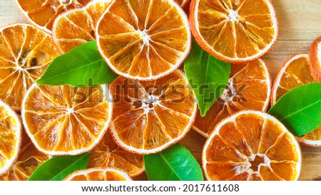 Dried orange slices on the wooden table. Dry citrus. Dried citrus fruits on the table. Orange slices top view. Still life citrus fruits photography.