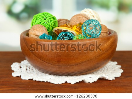 Dried oranges, wicker balls and other home decorations in wooden bowl, on bright background