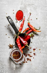 Dried peppers in a jar. On a stone background. Top view