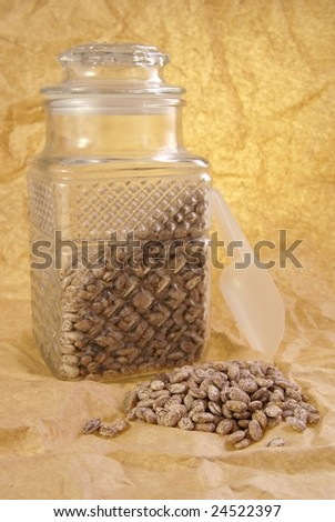 Dried pinto beans still life. Glass cut canister with beans, small scoop beside, and a pile of beans in front.