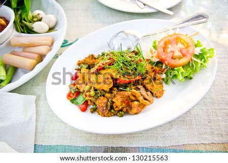 Dried pork with spicy curry on white plate in restaurant