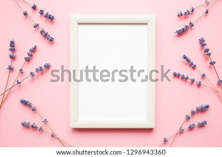 Dried purple lavender with blank white photo frame on pastel pink background. Mockup for positive idea. Empty place for inspirational, emotional, sentimental text, quote, sayings or picture. Flat lay.