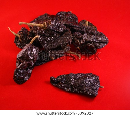 Dried red ancho chiles,		on red background, 	Seattle