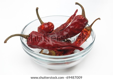 Dried red chili pepper  in glass bowl isolated on white background