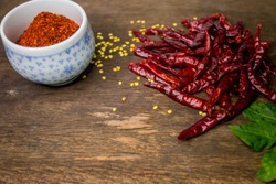 Dried red chilli, red chilli powder, chilli leaves on wooden table.