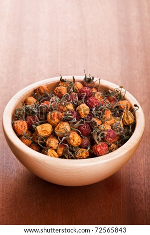 Dried rose hips in wooden bowl - stock photo