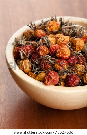 Dried rose hips in wooden bowl