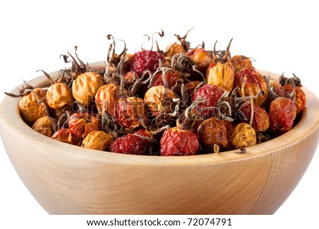 Dried rose hips in wooden bowl isolated on white