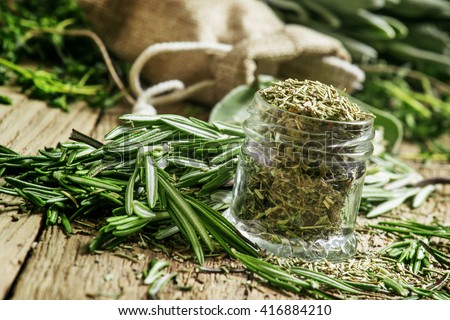Dried rosemary in a glass jar, branches of fresh rosemary, vintage wooden background, selective focus #416884210