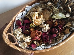 Dried roses, leaves and exotic flowers in a wicker basket on wooden table, a dyi scented potpourri autumnal vintage decoration for cosy interiors
