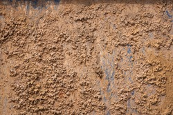 Dried roughly clay or mud on metal chemical waste containment storage tank's surface. Close-up photo.