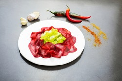 dried salted bresaola beef thinly sliced on a plate, appetizers plate of Bresaola