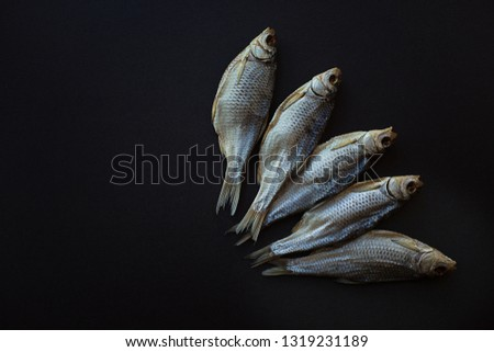 dried salted fish vobla on a black background. Caspian roach. Five pieces. Beer snack. Flat lay, top view, copy space
