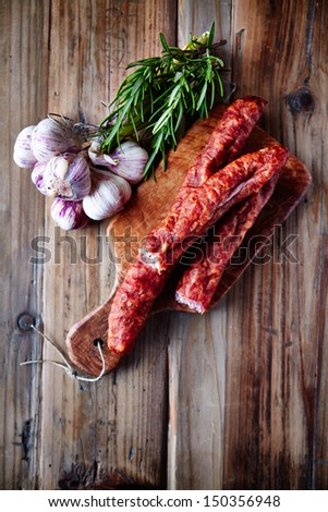 Dried sausage with garlic bulbs and fresh rosemary - stock photo