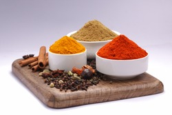 Dried Spices_Black pepper,Green pepper,Mace or Javiithri flower,Nutmeg,Clove,Cinnamon,Cardamom,Star Anise ,red chilli,turmeric powder,coriander powder arranged on a wooden surface with white texture