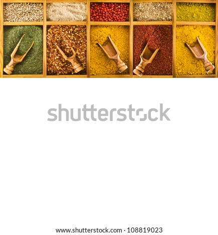 Dried spices for cooking different colors, in wooden boxes with wooden spoon isolated on white background