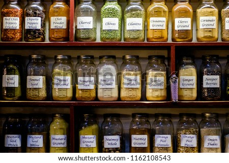 Dried spices in glass jars displayed on shelves.