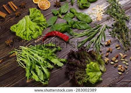 Dried spices, nuts and herbs on a wooden table.