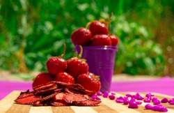 Dried strawberry chips with strawberry in purple pail on the background. Healthy snack. Proper nutrition.