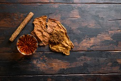 Dried tobacco leave and cut tobacco with cigar and whiskey rum on wood background on vintage dark table. top view space for text
