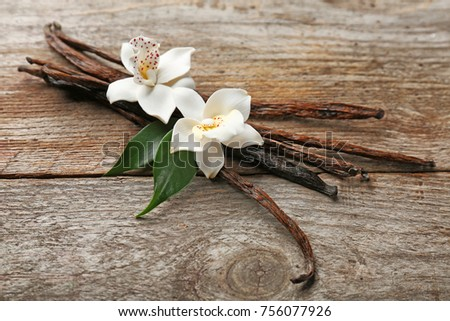 Dried vanilla pods and flowers on wooden background