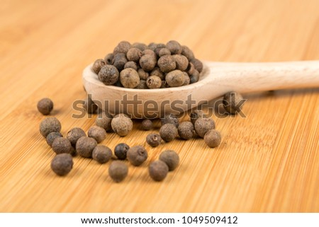 Dried whole allspice on a wood background #1049509412