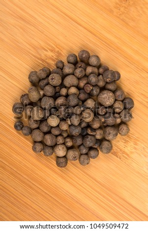 Dried whole allspice on a wood background #1049509472