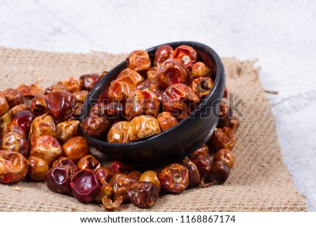 Dried whole round Chillis from low perspective isolated on wooden.