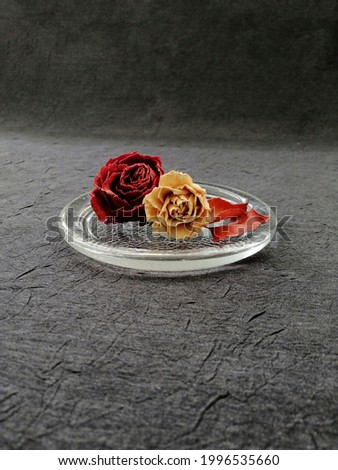 Dried yellow and red roses on plate Stok fotoğraf ©