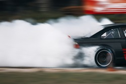 Drift car in motion drive fast with a lot of smoke. Car wheel spinning