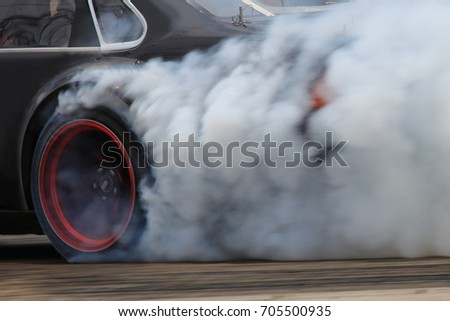 drift car motion spin rotating tire wheel with white smoke on the road.