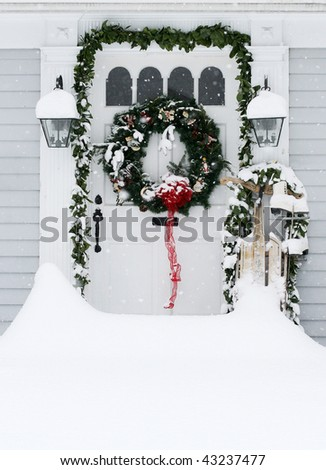 drifted snow in front of home entrance decorated for holidays