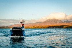 Drifting blue ferry ship between isle of Jura, in the background, and Isle of Skye, in Scotland at sunset time
