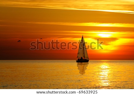 Drifting boat on a sunset - stock photo