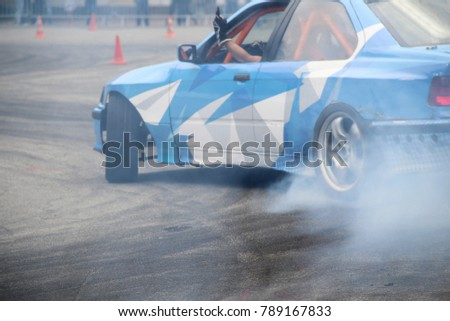 Drifting car in smoke from burning tires on the track in motion