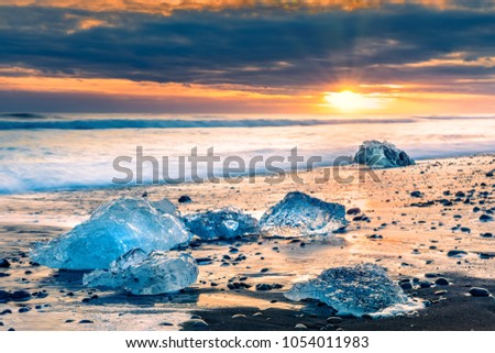 Stock Photo Drifting ice blocks on Diamond beach, at sunset, in Jokulsarlon, Iceland