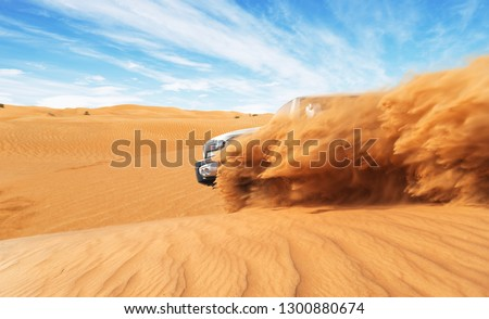 Drifting offroad car 4x4 in desert. Freeze motion of exploding sand powder into the air. Action and leasure activity.