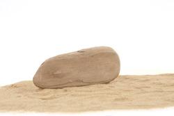 Driftwood on sand isolated on white background. Piece of coastal weathered wood on sand dune.