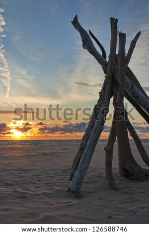 Driftwood tipi on beach with dramatic sunlight