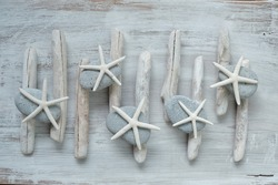 Driftwood. White sea driftwood, gray stones and white starfishes on a  shabby chic wooden background.Home decor and wallpaper in a nautical style.Driftwood decor in minimalism style in gray tones